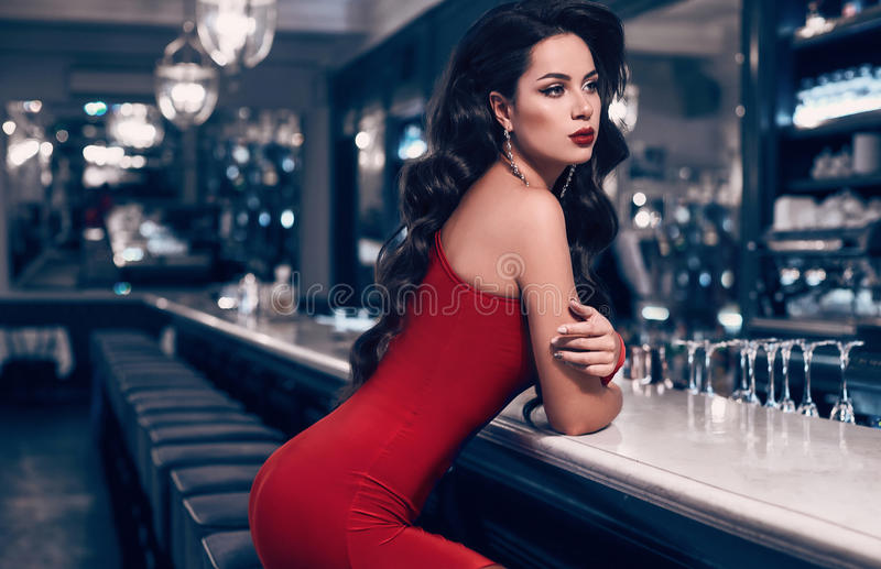 Gorgeous beauty young brunette woman in red dress. Standing at the bar in luxury interior stock image