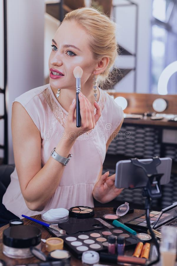Gorgeous blogger making video about trends in cosmetics. Cosmetics trends. Gorgeous good-looking beauty blogger making her next video about trends in cosmetics stock photo