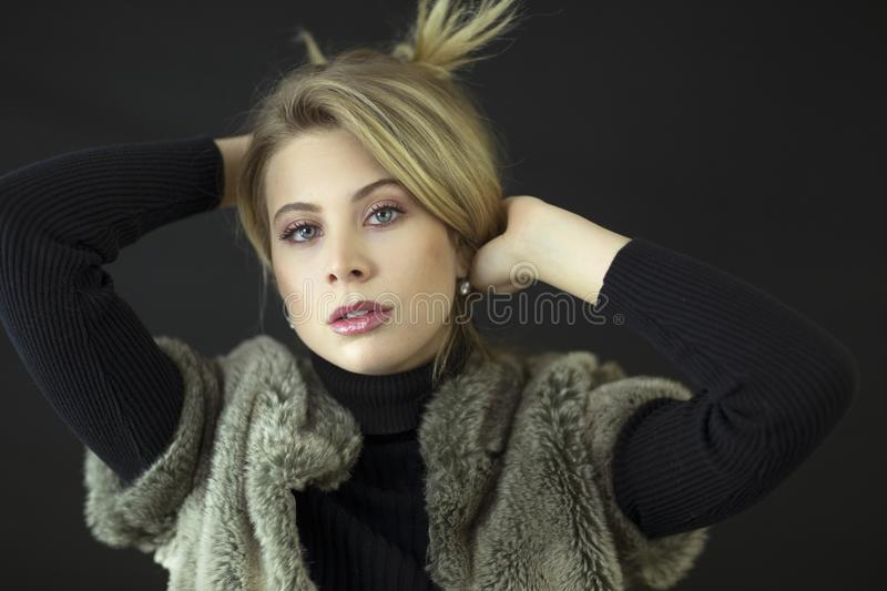 A gorgeous blond model with blue eyes and black turtleneck and fur vest in studio. royalty free stock photos