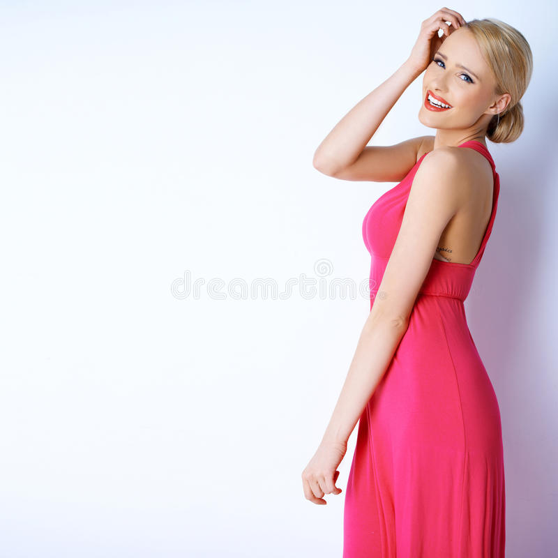 Gorgeous blond woman posing in pink dress stock image