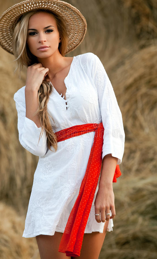 Gorgeous blond in sunhat. Gorgeous young woman with long blond hair wearing a straw sunhat and short white dress tied with a red sash stock photos