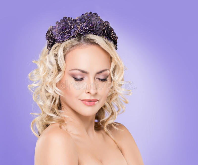 Beauty portrait of attractive blond girl with curly hair and a beautiful headband over magenta purple violet background. royalty free stock images