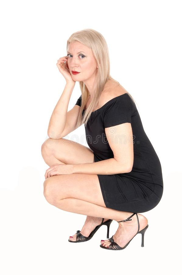 Gorgeous blond woman crouching on floor. A beautiful blond woman in a short black dress crouching on the floor.in high heels, hand on her face, isolated for royalty free stock images