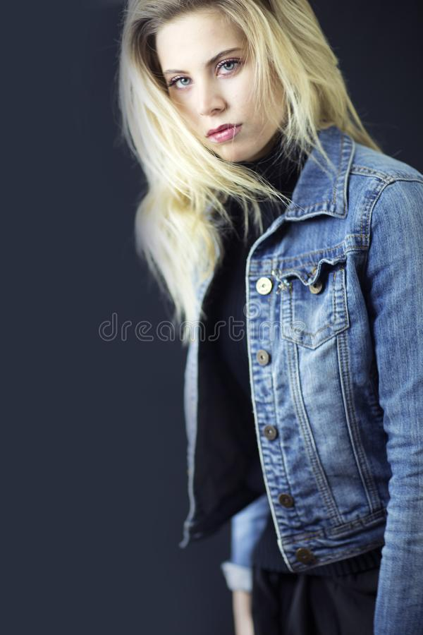 A gorgeous blond woman with messy hair, black turtleneck and jean jacket. royalty free stock images