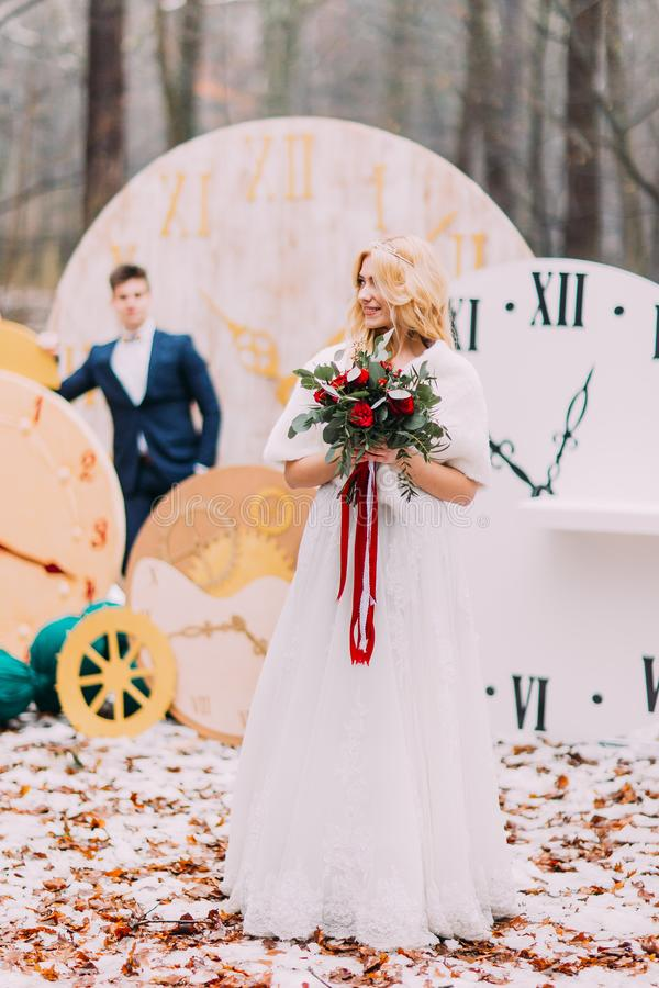 Gorgeous blonde bride with bouquet in the autumn forest. Silhouette of groom on background. royalty free stock images