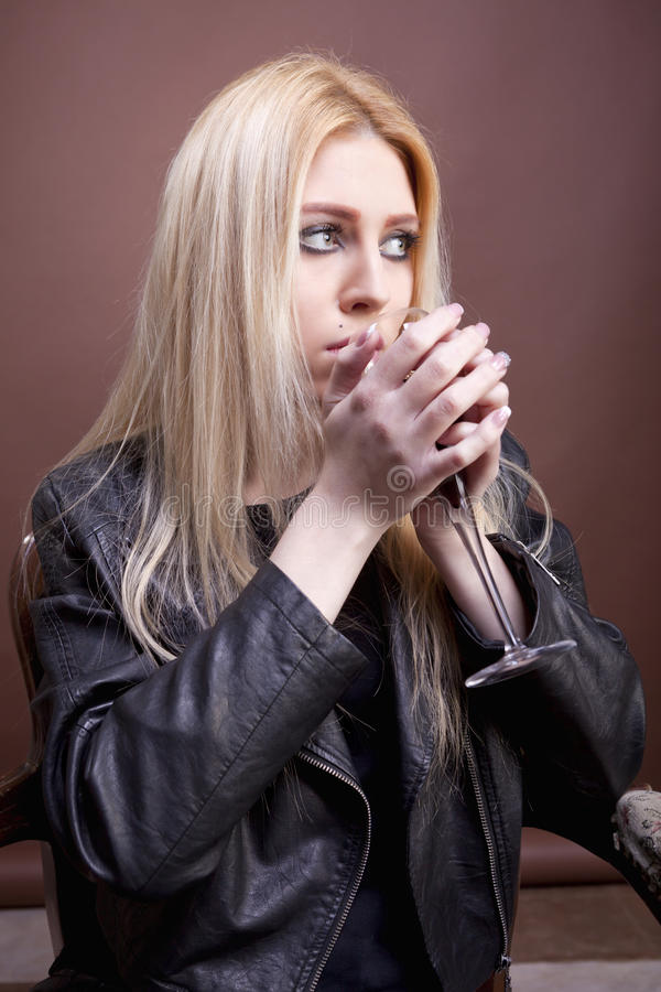 Gorgeous blonde girl drinking from a glass royalty free stock image