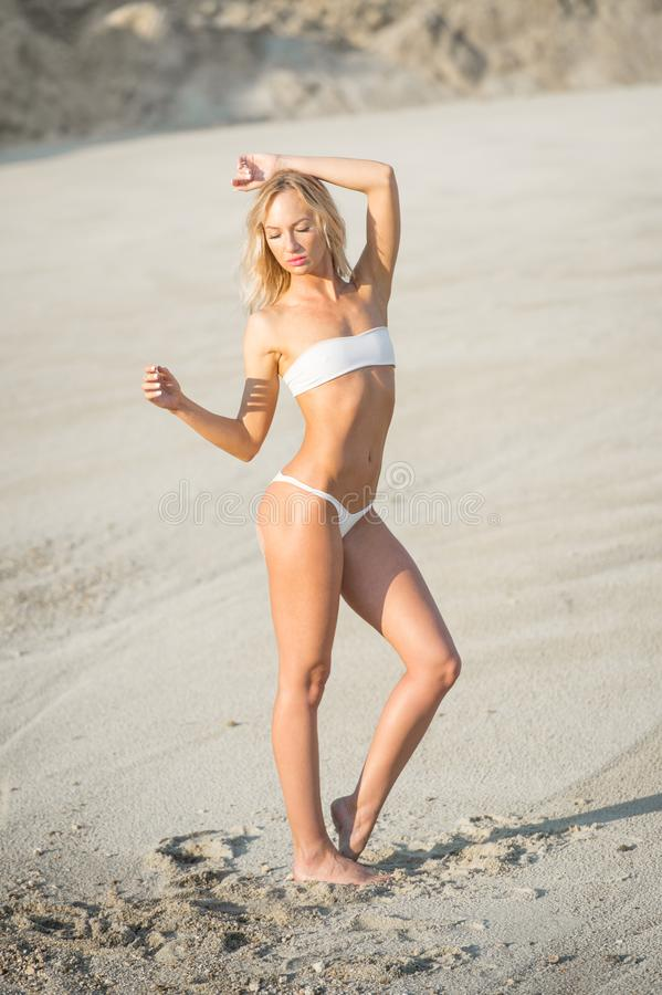 Gorgeous blonde girl model with perfect body posing on the beach stock image