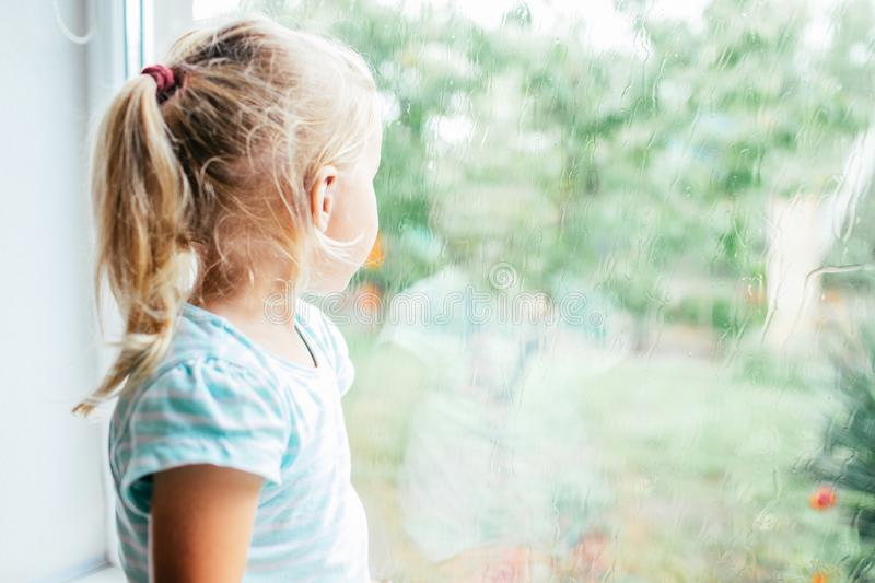 A gorgeous blonde little girl with ponytale staring out of the window on a wet, cold rainy summer day stock images