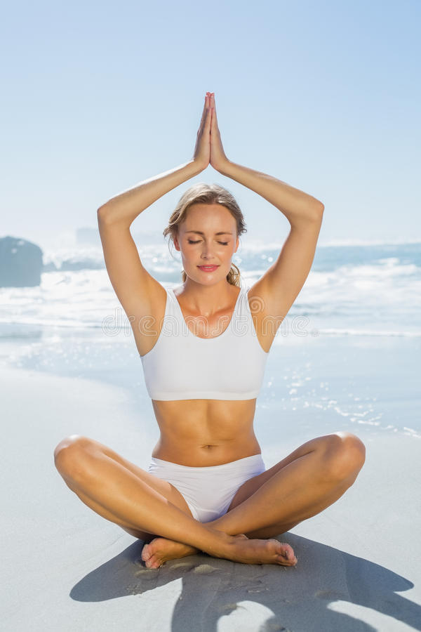 Gorgeous blonde in lotus pose by the sea royalty free stock image
