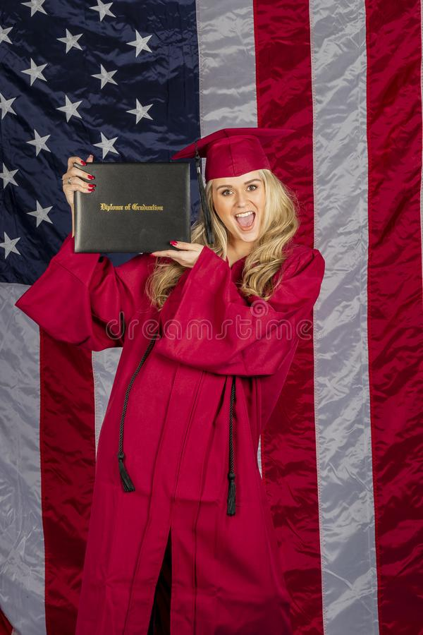 Beautiful Blonde Model Posing With A Diploma With An American Flag In The Background stock photos