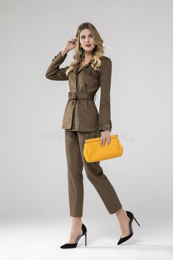 Free Gorgeous Blonde Model Posing In Olive Suit And Chic Yellow Handbag. Stock Image - 183207981