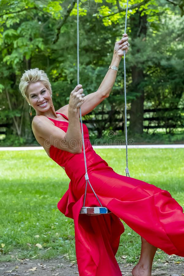 Gorgeous Blonde Model Posing Outdoors Wearing A Red Evening Gown stock photo