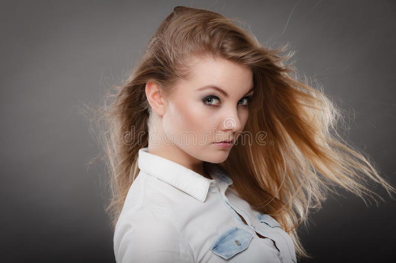 Gorgeous blonde woman with open waving hair. Hairstyle and haircare concept. Portrait of blonde charming attractive young lady with open waving hair. Woman with stock photography