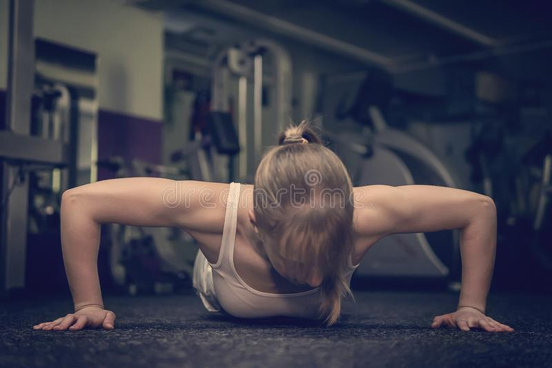 Gorgeous blonde woman warming up and doing some push ups a the gym, Sports concept healthy lifestyle and fitness royalty free stock photo