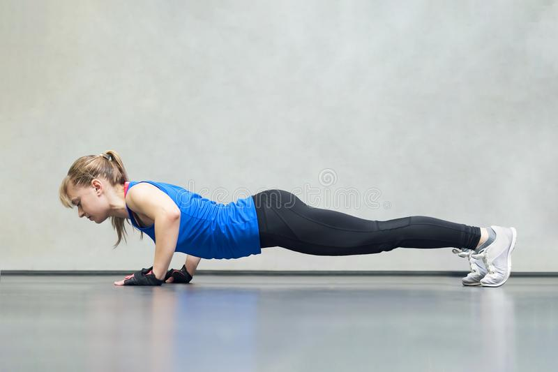 Gorgeous blonde woman warming up and doing some push ups a the gym, Sports concept healthy lifestyle and fitness. side view royalty free stock images