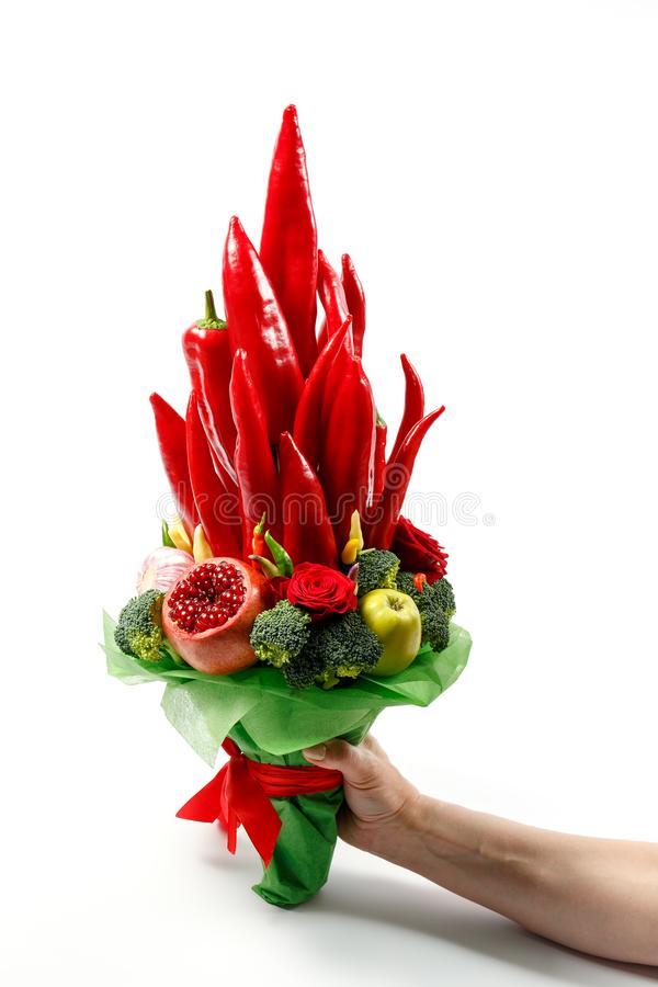 Gorgeous bouquet consisting of paprika, broccoli, apples and other vegetables and fruits in hand as a gift on a white background royalty free stock photography
