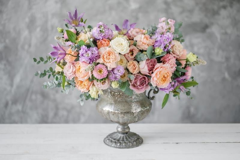 Gorgeous bouquet of different flowers. floral arrangement in vintage metal vase. table setting. lilac and peach color royalty free stock photos