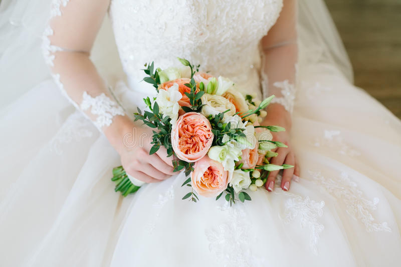 Gorgeous bouquet of white and orange flowers in the hands of the charming bide in a white dress. Gorgeous bouquet of white and orange flowers in the hands of stock images
