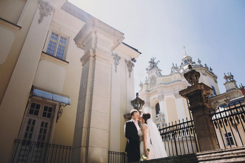 Gorgeous bride in amazing gown and stylish groom kissing and embracing in sunny street at old building. Beautiful happy wedding stock image