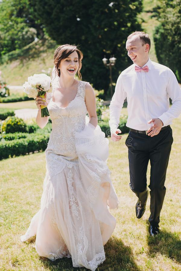 Gorgeous bride in amazing gown and stylish groom running and laughing in sunny park. Beautiful happy wedding couple enjoying time royalty free stock image