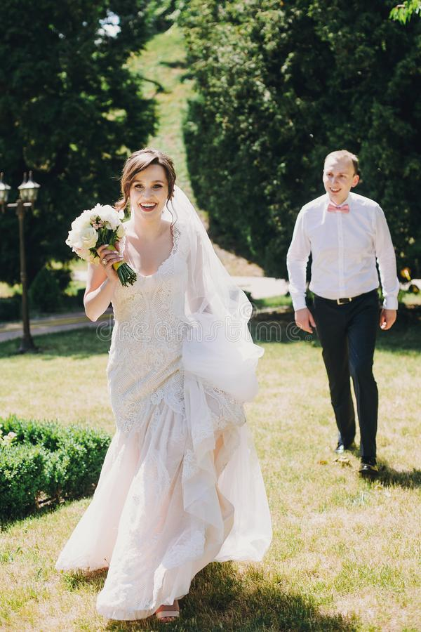 Gorgeous bride in amazing gown and stylish groom running and laughing in sunny park. Beautiful happy wedding couple enjoying time royalty free stock images