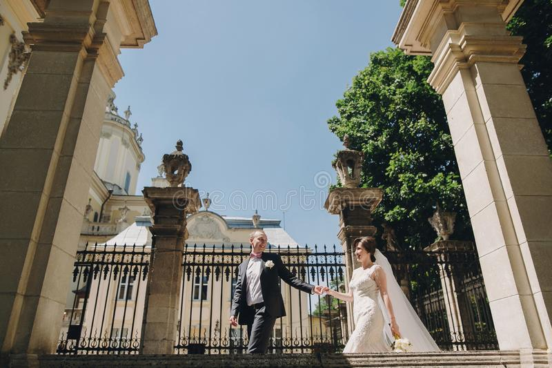 Gorgeous bride in amazing gown and stylish groom walking and smiling in sunny city street. Beautiful happy wedding couple enjoying stock image