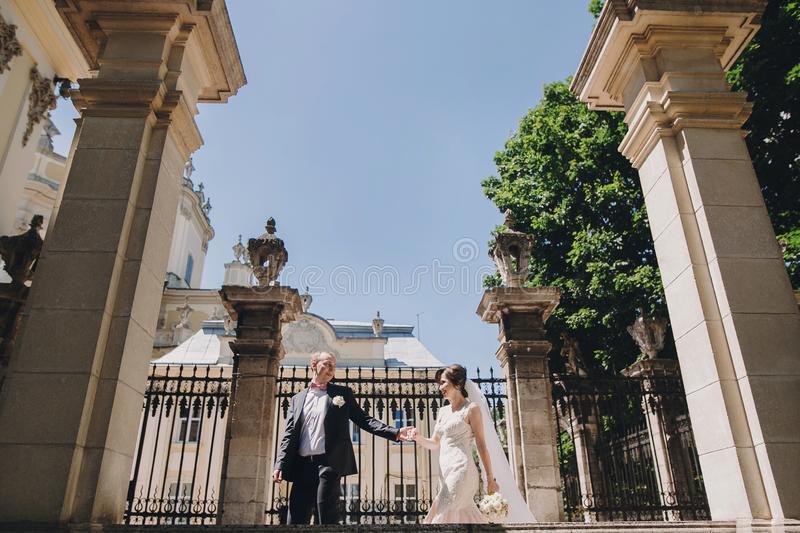Gorgeous bride in amazing gown and stylish groom walking and smiling in sunny city street. Beautiful happy wedding couple enjoying stock photography