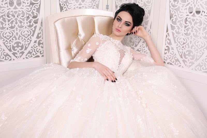 Gorgeous bride with dark hair in luxuious wedding dress. Fashion studio photo of gorgeous bride with dark hair in luxuious wedding dress royalty free stock photo