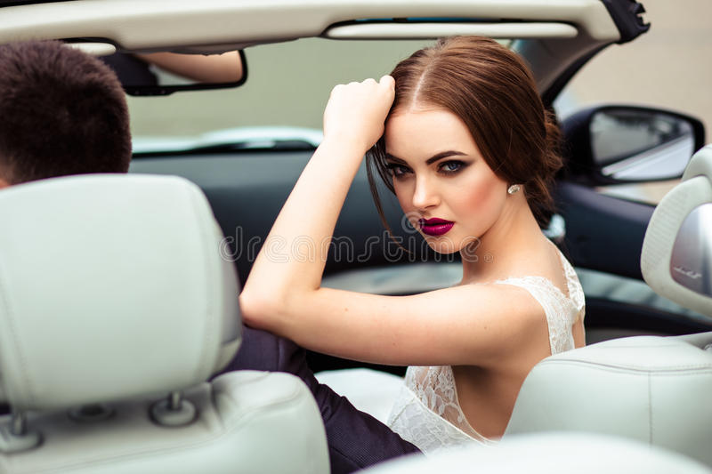 Gorgeous bride with fashion makeup and hairstyle in a luxury wedding dress with handsome groom near white cabriolet car. Beauty portrait stock image