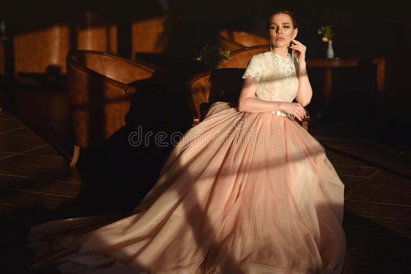 Gorgeous bride in luxurious puffy wedding dress with veiling skirt sitting in the armchair royalty free stock images