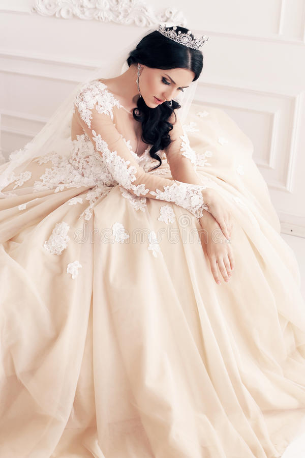 Gorgeous bride in luxurious wedding dress with accessories. Fashion interior photo of gorgeous bride in luxurious wedding dress with accessories royalty free stock photography