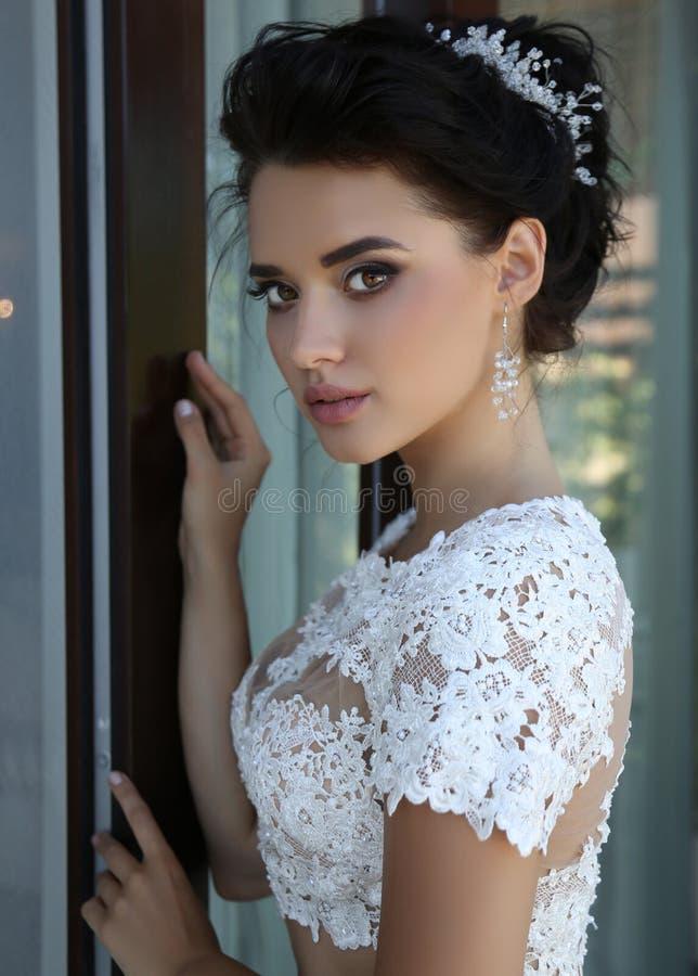 Gorgeous bride in luxurious wedding dress. Fashion interior photo of gorgeous bride in luxurious wedding dress posing at balcony royalty free stock image