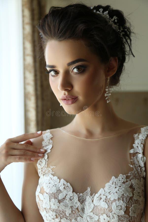 Gorgeous bride in luxurious wedding dress. Fashion interior photo of gorgeous bride in luxurious wedding dress posing in bedroom royalty free stock photo