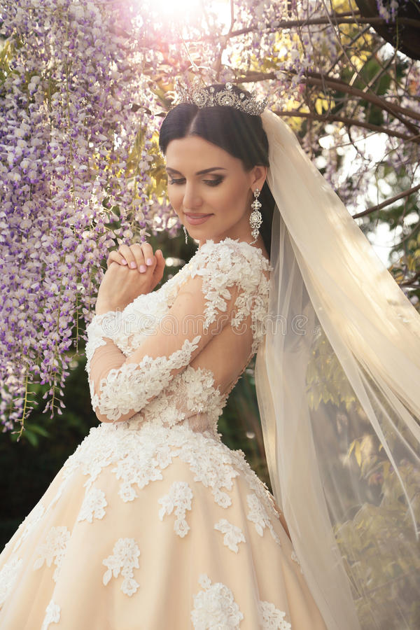 Gorgeous bride in luxurious wedding dress, posing in blossom garden. Fashion outdoor photo of gorgeous bride in luxurious wedding dress, posing in blossom garden royalty free stock photos