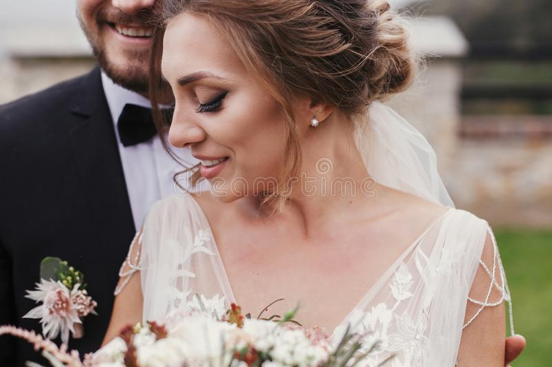 Gorgeous bride with modern bouquet and stylish groom gently hugging and smiling outdoors. Sensual wedding couple embracing. Roman royalty free stock photography