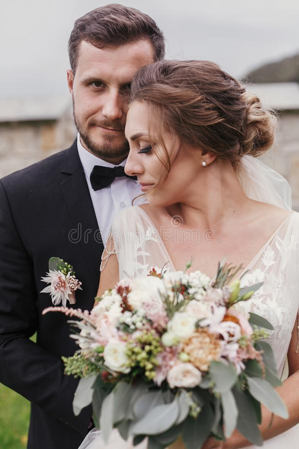 Gorgeous bride with modern bouquet and stylish groom gently hugging and smiling outdoors. Sensual wedding couple embracing. Roman stock photo