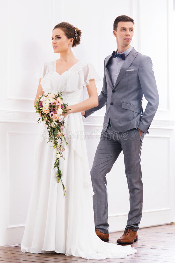 Gorgeous bride with a posy and a handsome groom in retro interior stock image