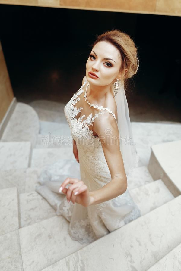 Gorgeous bride in sexy white wedding dress posing on marble staircase indoors, beautiful blonde bride portrait on stairs in stock photo
