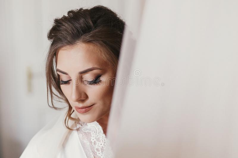 Gorgeous bride in silk robe holding stylish wedding dress in room in the morning. Happy Bride and her beautiful wedding gown royalty free stock photography