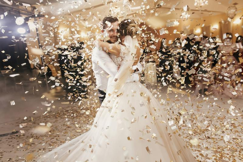 Gorgeous bride and stylish groom dancing under golden confetti a stock image