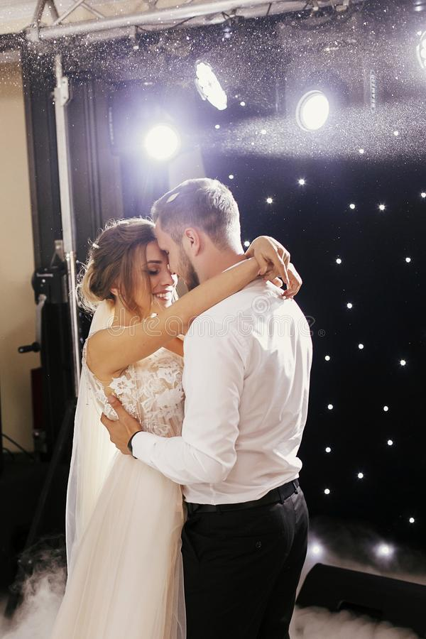 Gorgeous bride and stylish groom gently dancing at wedding reception. Happy wedding couple performing first dance in restaurant. stock photo