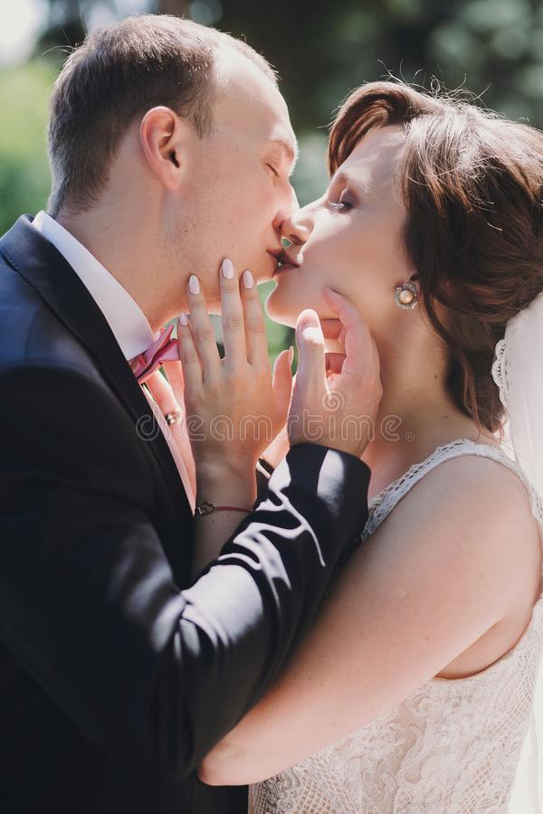 Gorgeous bride and stylish groom gently hugging and embracing in sunny street. Portraits of beautiful happy wedding couple kissing stock photos