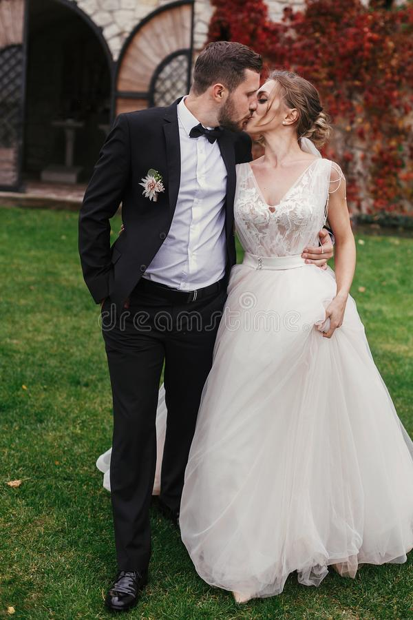 Gorgeous bride and stylish groom gently hugging and kissing outdoors. Sensual wedding couple embracing. Romantic moments of newly royalty free stock images