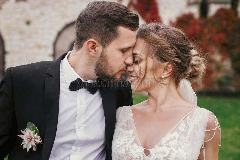 Gorgeous bride and stylish groom gently hugging and kissing outdoors. Sensual wedding couple embracing. Romantic moments of newly stock images