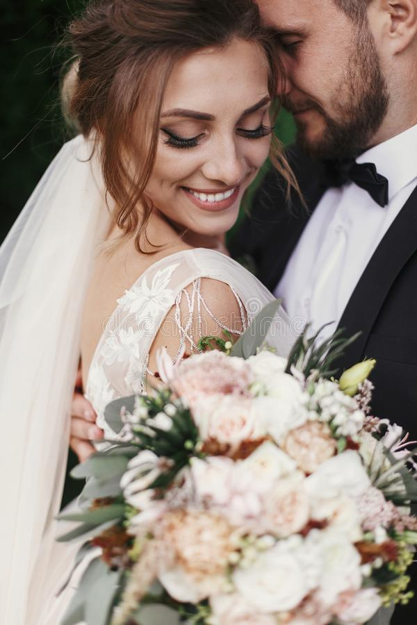 Gorgeous bride and stylish groom gently hugging and smiling on b stock images