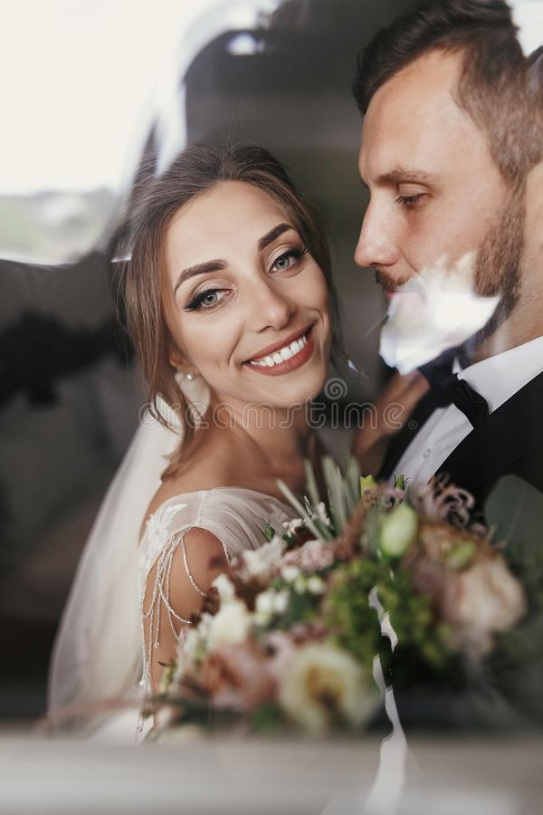 Gorgeous bride and stylish groom gently hugging at window. Sensual happy wedding couple embracing and smiling in light. Romantic royalty free stock photo