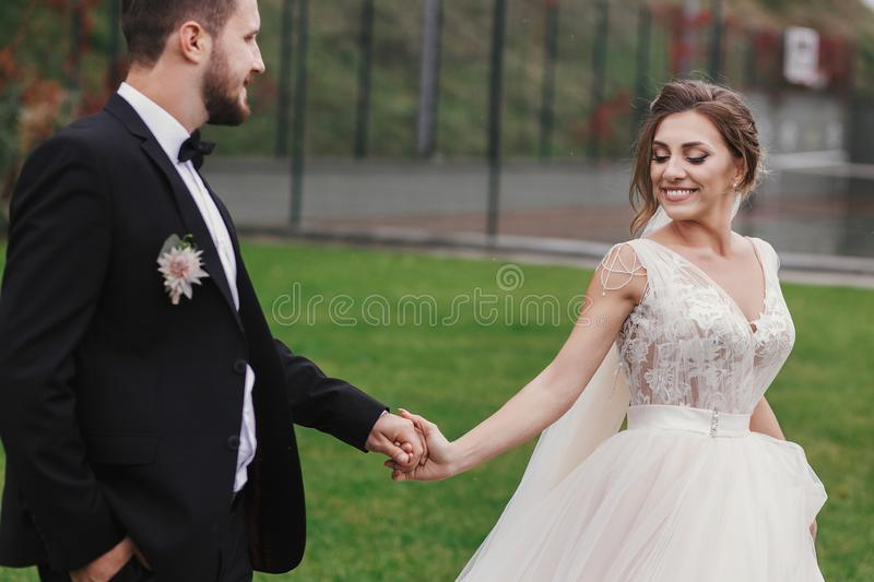 Gorgeous bride and stylish groom holding hands and walking at wa royalty free stock images