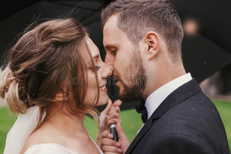 Gorgeous bride and stylish groom passionately kissing under umbrella in rainy outdoors. Sensual wedding couple embracing. royalty free stock photos