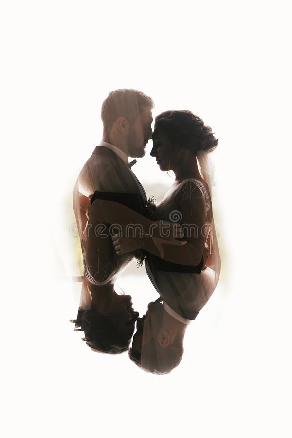 Gorgeous bride and stylish groom silhouettes gently hugging. Double exposure of sensual wedding couple embracing. Romantic moment royalty free stock photo