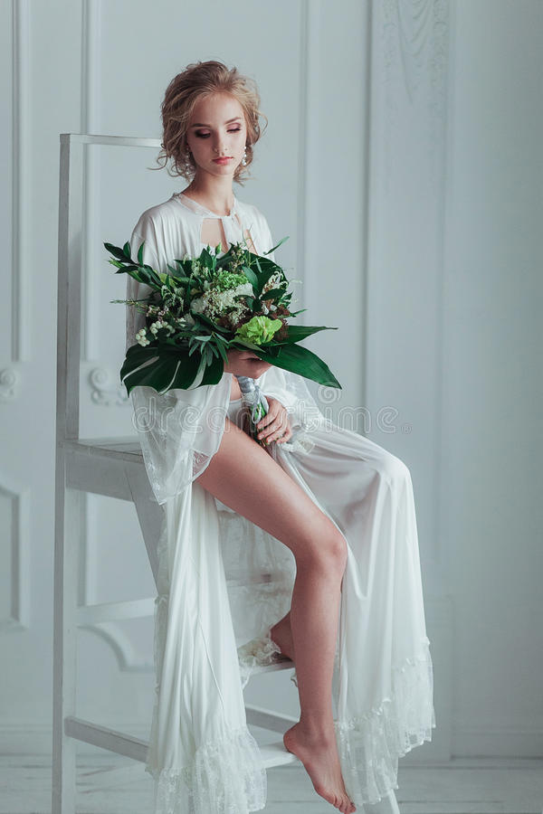Gorgeous bride with wedding bouquet sitting on the decorated ladder stock photography